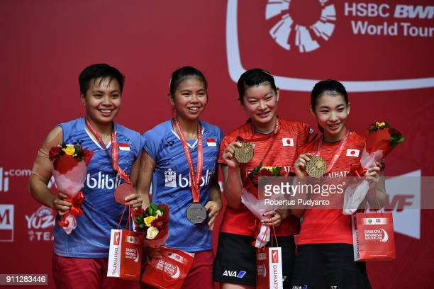 Gold medalist Misaki Matsutomo and Ayaka Takahashi of Japan and silver medalist Greysia Polii and Apriyani Rahayu of Indonesia celebrate on the...