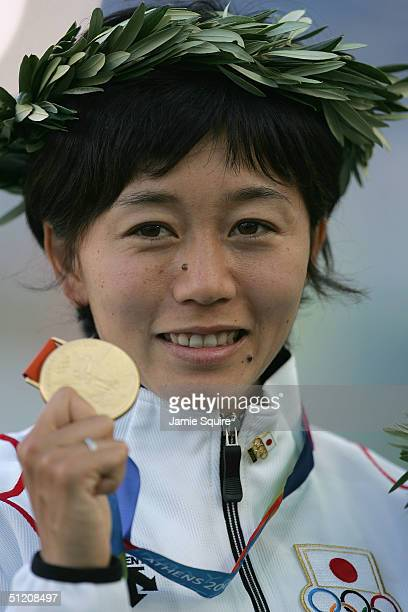 Gold medalist Mizuki Noguchi of Japan celebrates on the podium during the medal ceremony of the women's marathon event on August 23 2004 during the...