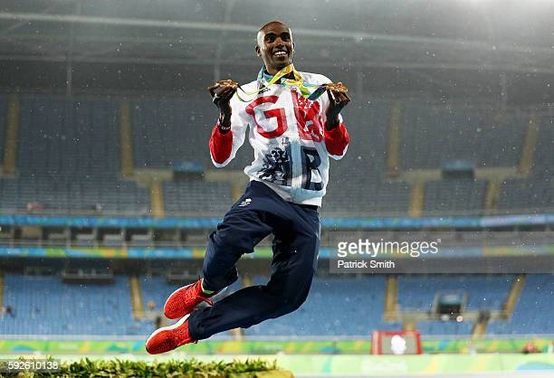 Gold medalist Mohamed Farah of Great Britain holds both his 5000 meter and 10000 meter gold medals on the podium during the medal ceremony for the...