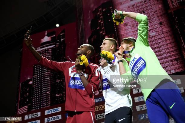 Gold medalist Mutaz Essa Barshim of Qatar, silver medalist Mikhail Akimenko of Authorised Neutral Athletes, and bronze medalist Ilya Ivanyuk of...