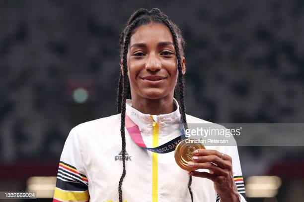 Gold medalist Nafissatou Thiam of Team Belgium holds up her medal on the podium during the medal ceremony for the Women's Heptathlon on day fourteen...