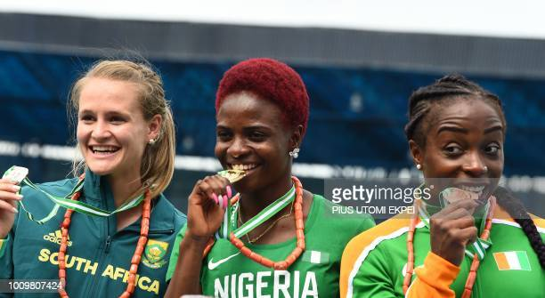 Gold medalist Nigeria's Oluwatobiloba Amusan poses with silver medalist South Africa's Steenkamp Rikennete and bronze medalist Ivorian Rosvitha Okou...