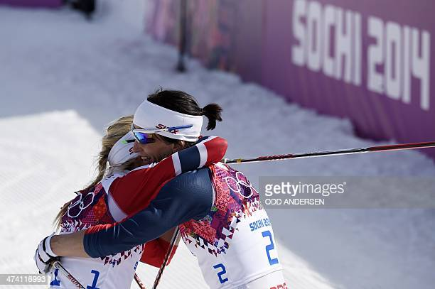 Gold medalist Norway's Marit Bjoergen hugs silver medalist Norway's Therese Johaug at the finish line in the Women's CrossCountry Skiing 30km Mass...