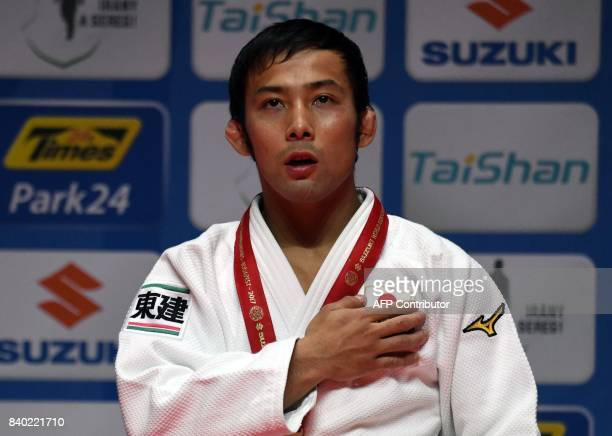 Gold medalist of Japan's Naohisa Takato sings his national anthem on the podium during the medal ceremony of the mens 60kg category at the World Judo...