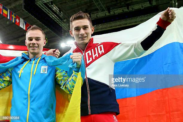 Gold medalist Oleg Verniaiev of Ukraine and bronze medalist David Belyavskiy of Russia pose for photographs after competing in the Parallel Bars...