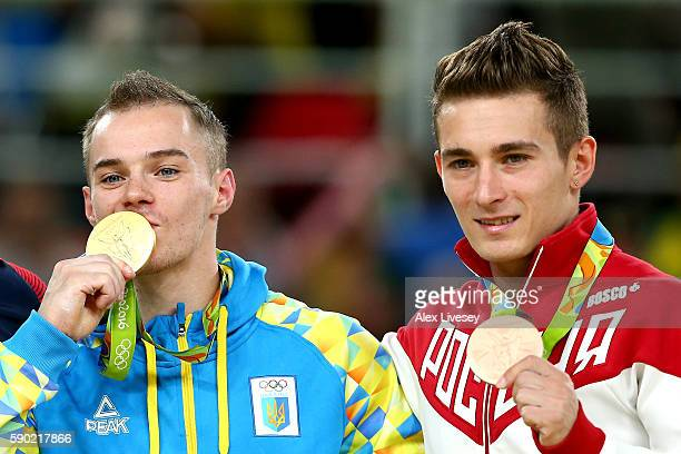 Gold medalist Oleg Verniaiev of Ukraine and bronze medalist David Belyavskiy of Russia pose for photographs at the medal ceremony for the Parallel...