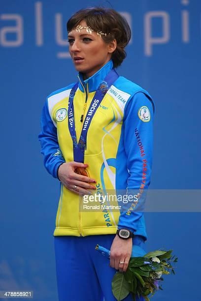 Gold medalist Oleksandra Kononova covers her medal as she sings the national anthem at the medal ceremony for the Women's 125km Standing Biathlon...
