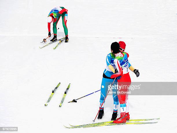 Gold medalist Oleksandra Kononova of Ukraine embraces silver medalist Shoko Ota of Japan after the in the Women's 1km Standing CrossCountry Sprint...