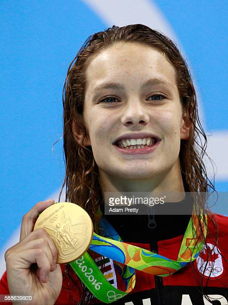 Gold medalist Penny Oleksiak of Canada celebrates on the podium during the medal ceremony for the Women's 100m Freestyle Final on Day 6 of the Rio...