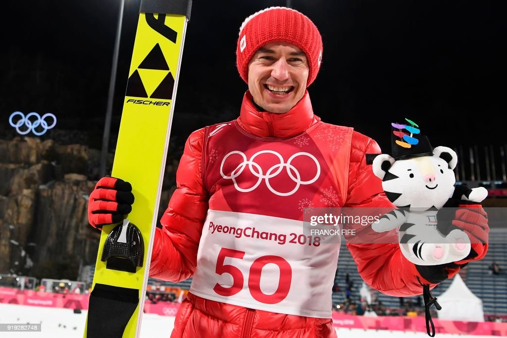 TOPSHOT - Gold medalist, Poland's Kamil Stoch pose for a picture after the victory ceremony following the men's large hill individual ski jumping event during the Pyeongchang 2018 Winter Olympic Games on February 17, 2018, in Pyeongchang. /