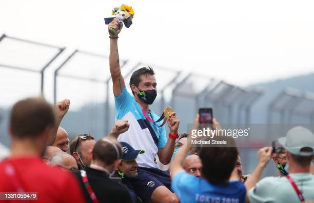 Gold medalist Primoz Roglic of Team Slovenia is lifted up by his team to celebrate their victory after the Men's Individual time trial on day five of...