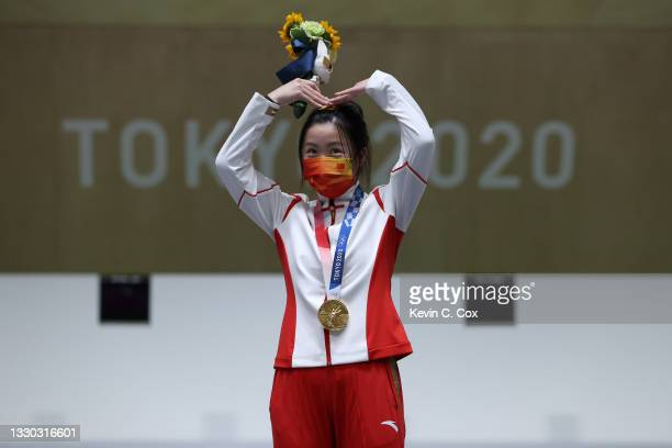 Gold Medalist Qian Yang of Team China poses on the podium during the medal ceremony for the 10m Air Rifle Women's event on day one of the Tokyo 2020...