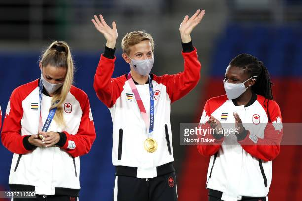 Gold medalist Quinn of Team Canada waves with their gold medal during the Women's Football Competition Medal Ceremony on day fourteen of the Tokyo...