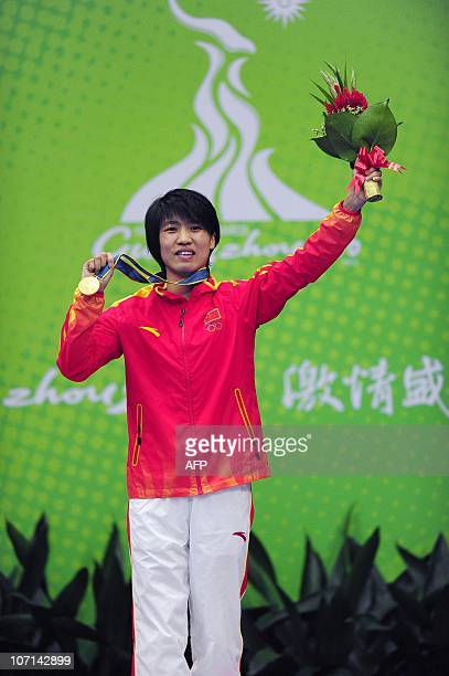 Gold medalist Ren Cancan of China poses on the pedium during the ceremony for the women's 4851kg boxing final at the 16th Asian Games in Guangzhou on...