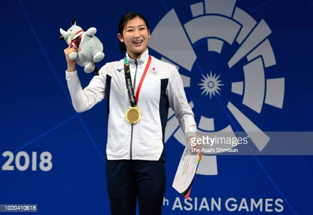 Gold medalist Rikako Ikee of Japan celebrates on the podium at the medal ceremony for the Swimming Women's 100m Freestyle at the GBK Aquatics Center...