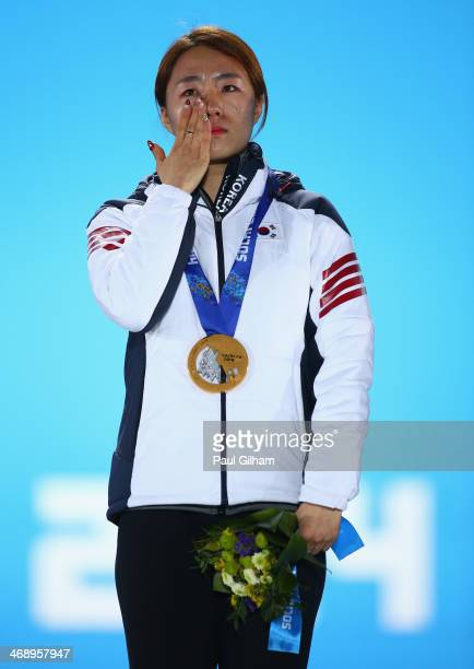 Gold medalist Sang Hwa Lee of South Korea celebrates during the medal ceremony for the Women's 500m on day five of the Sochi 2014 Winter Olympics at...