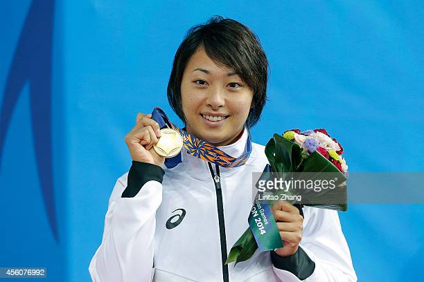 Gold medalist Satomi Suzuki of Japan celebrates during the medal ceremony after the swimming Women's 50m Breaststroke Final during the 2014 Asian...
