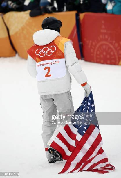 Gold medalist Shaun White of the United States drags the American flag as he celebrates during the Snowboard Men's Halfpipe Final on day five of the...