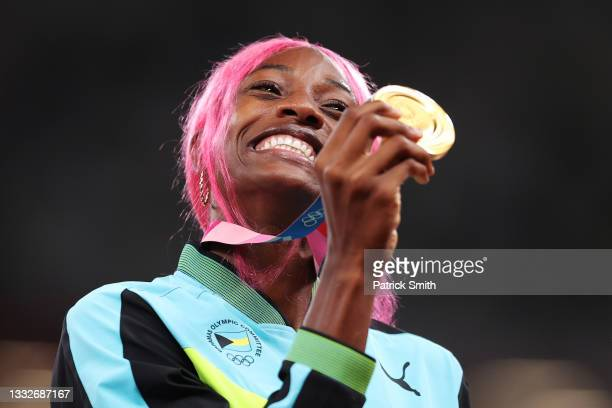 Gold medalist Shaunae Miller-Uibo of Team Bahamas holds up her medal on the podium during the medal ceremony for the Women's 400m on day fourteen of...