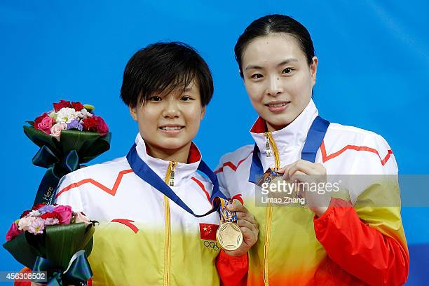Gold medalist Shi Tingmao and Wu Minxia of China celebrates during the medal ceremony after the Women's Synchronised 3m Springboard Final in day ten...