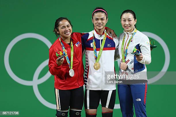 Gold medalist ShuChing Hsu of Chinese Taipei silver medalist Hidilyn Diaz of the Philippines and bronze medalist Jin Hee Yoon of Korea celebrate on...