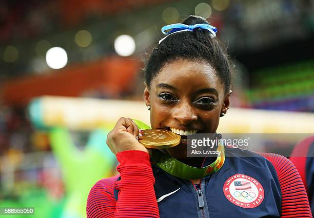 Gold medalist Simone Biles of the United States poses for photographs after the medal ceremony for the Women's Individual All Around on Day 6 of the...