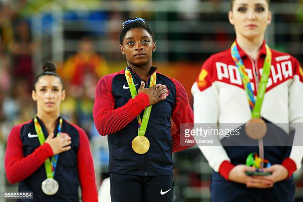 Gold medalist Simone Biles of the United States stands on the podium for the national anthem at the medal ceremony for the Women's Individual All...