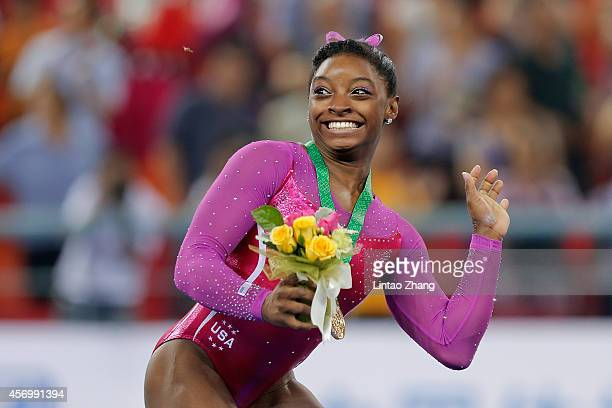 Gold medalist Simone Biles of United States avoids a bee during the medal ceremony after the Women's AllAround Final in day four of the 45th Artistic...