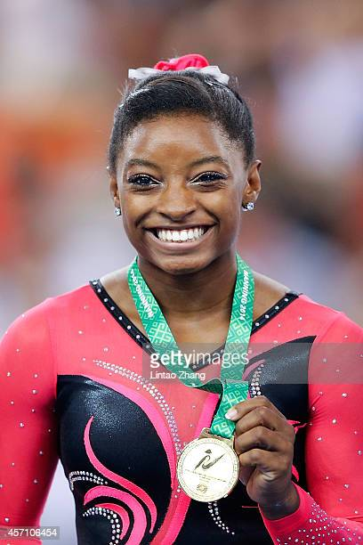Gold medalist Simone Biles of United States celebrates during the medal ceremony after Women's Balance Beam Final on day six of the 45th Artistic...