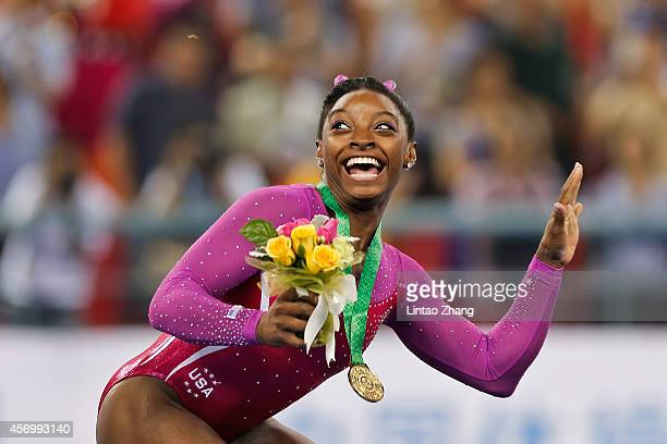 Gold medalist Simone Biles of United States scared form a bee fly during the medal ceremony after the Women's AllAround Final in day four of the 45th...