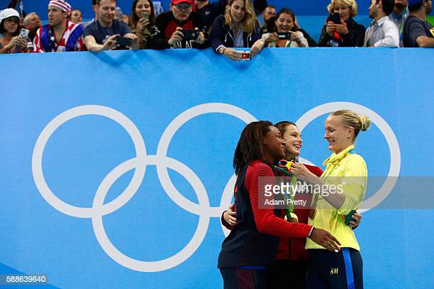 Gold medalist Simone Manuel of the United States gold medalist Penny Oleksiak of Canada and bronze medalist Sarah Sjostrom of Sweden celebrate on the...