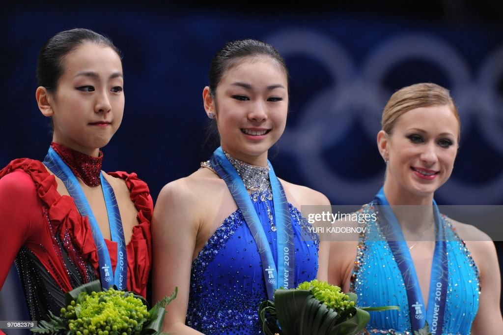 Gold medalist South Korea's Yu-Na Kim (C), silver medalist Japan's Mao Asada (L) and bronze medalist Canada's Joannie Rochette stand on the podium in the award ceremony of the Women's Figure Skating event, at the Pacific Coliseum in Vancouver during the XXI Winter Olympics, on February 25, 2010.