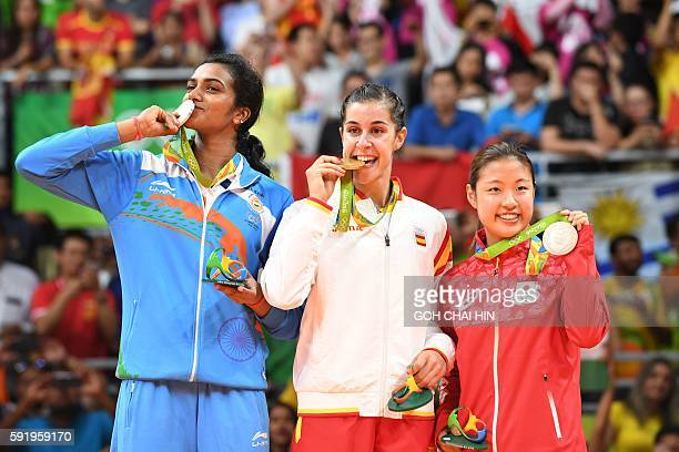 Gold medalist Spain's Carolina Marin Silver medalist India's Pusarla V Sindhu and Bronze medalist Japan's Nozomi Okuhara stand with their medals on...