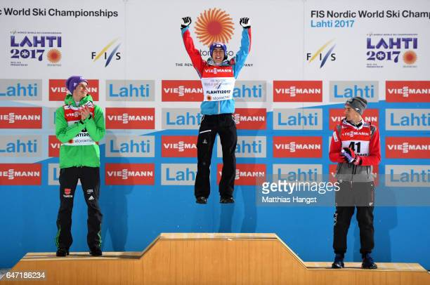 Gold medalist Stefan Kraft of Austria celebrates alongside silver medalist Andreas Wellinger of Germany and bronze medalist Piotr Zyla of Poland...