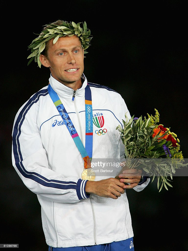 Gold medalist Stefano Baldini of Italy celebrates on the podium during the medal ceremony of the men's marathon on August 29, 2004 during the Athens 2004 Summer Olympic Games at the Olympic Stadium in the Sports Complex in Athens, Greece. Mebrahtom Keflezighi of USA came second and Vanderlei Lima of Brazil came third.