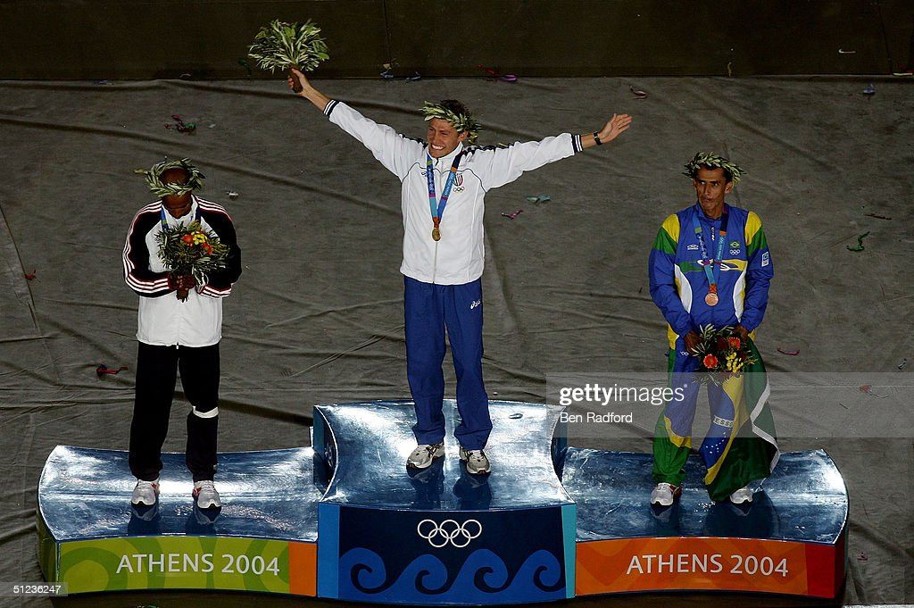 Gold medalist Stefano Baldini of Italy, silver medalist Mebrahtom Keflezighi of USA (L) and bronze medalist Vanderlei Lima of Brazil celebrate on the podium during the medal ceremony of the men's marathon on August 29, 2004 during the Athens 2004 Summer Olympic Games at the Olympic Stadium in the Sports Complex in Athens, Greece.