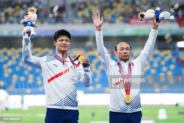Gold medalist Su Bingtian of Guangdong and his coach Yuan Guoqiang celebrate on the podium after the Men's 100m Sprint Final during China's 14th...