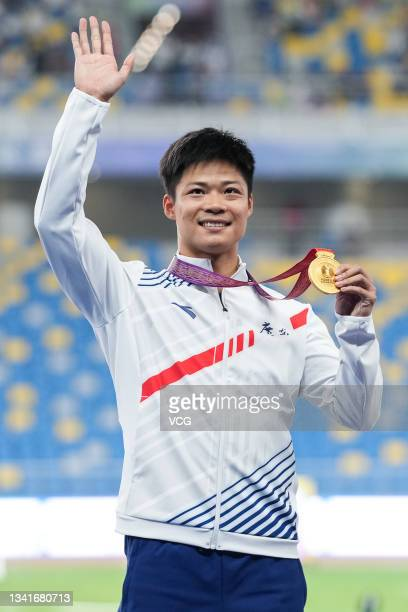 Gold medalist Su Bingtian of Guangdong celebrates on the podium after the Men's 100m Sprint Final during China's 14th National Games at Xi'an Olympic...