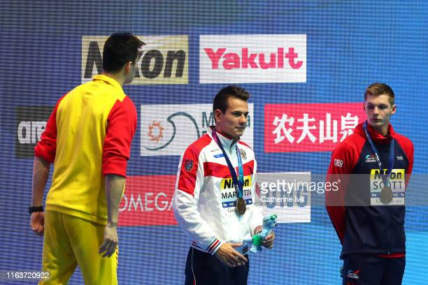 Gold medalist Sun Yang of China bronze medalists Martin Malyutin of Russia and Duncan Scott of Great Britain interact during the medal ceremony for...