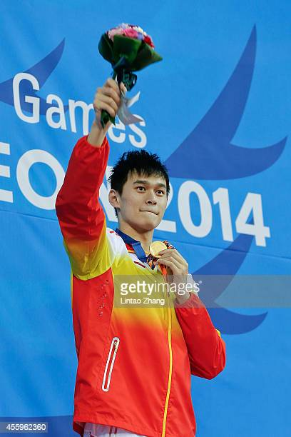 Gold medalist Sun Yang of China celebrates during the medal ceremony after the swimming Men's 400m Freestyle Final during the day four of 2014 Asian...
