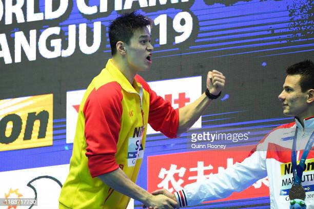 Gold medalist Sun Yang of China shakes hands with bronze medalist Martin Malyutin of Russia during the medal ceremony for the Men's 200m Freestyle...