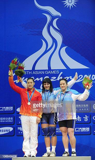 Gold medalist Svetlana Podobedova of Kazakhstan celebrates on the pedium with silver medalist Cao Lei of China and bronze medalist Tatyana Khromova...