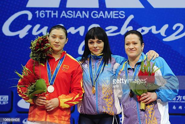 Gold medalist Svetlana Podobedova of Kazakhstan poses on the pedium with silver medalist Cao Lei of China and bronze medalist Tatyana Khromova of...