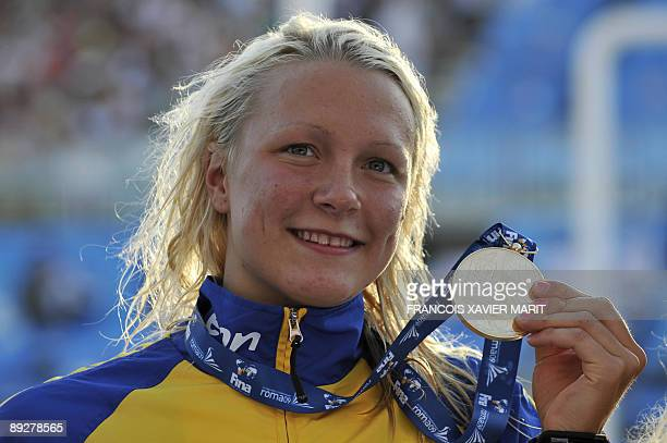 Gold medalist Sweden's Sarah Sjostrom celebrates on the podium of the women's 100m butterfly final on July 27 2009 at the FINA World Swimming...