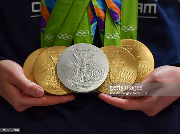 S gold medalist swimmer Katie Ledecky shows her four golds and one silver medal while speaking to the media after arriving at Dulles Airport from the...