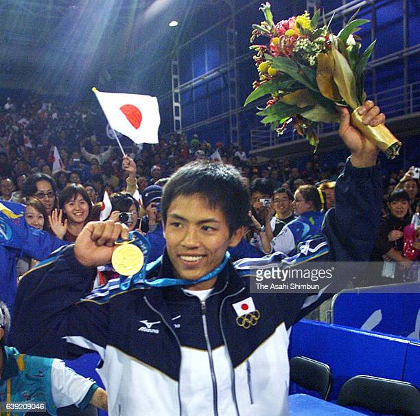 Gold medalist Tadahiro Nomura of Japan celebrates after the medal ceremony for the Men's Judo 60kg during the Sydney Olympics at the Sydney...