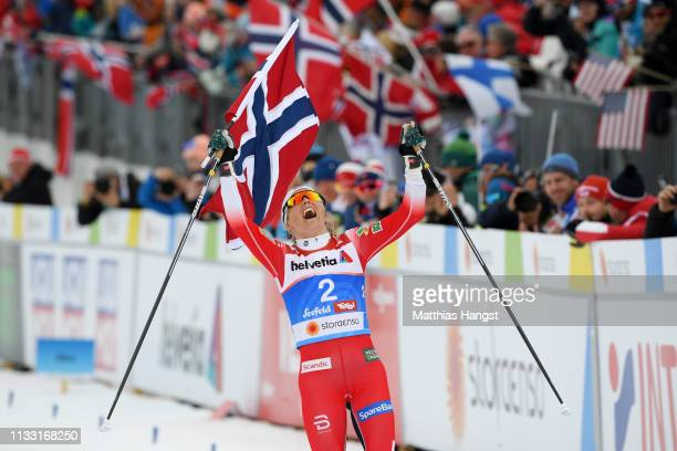 Gold medalist Therese Johaug of Norway celebrates as she approaches the finish line to win the Women's Cross Country 30k race during the FIS Nordic...