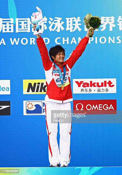 Gold medalist Tingmao Shi of China salutes the crowd at the medal ceremony for the Women's 1m Springboard during Day Four of the 14th FINA World...