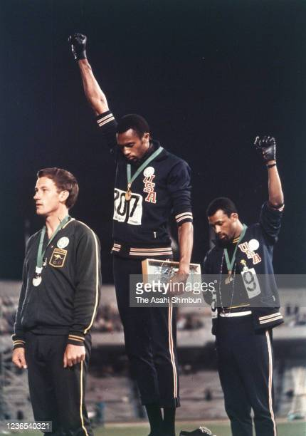 Gold medalist Tommie Smith and bronze medalist John Carlos of the United States raise their fists on the podium at the medal ceremony for the...