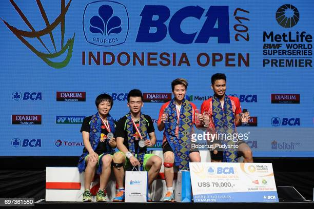 Gold medalist Tontowi Ahmad and Liliyana Natsir of Indonesia and silver medalist Zheng Siwei and Chen Qingchen of China celebrate on the podium...